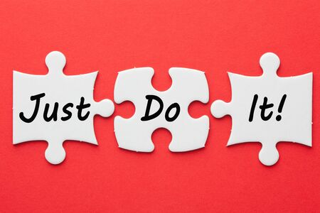 Just Do It text on 3 pieces paper puzzle on a red background. Business concept.