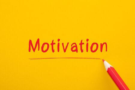 The word Motivation written with red pencil on yellow background. Business Concept.