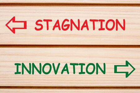 Opposite words Stagnation and Innovation written on wood wall  decor. 版權商用圖片