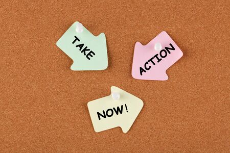 Take Action Now text on color reminder notes with pin on cork board. Business concept.