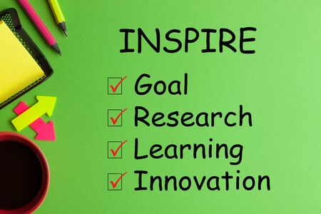 Inspire list with conceptual words, cup of coffee and office supplies on green background. Zdjęcie Seryjne