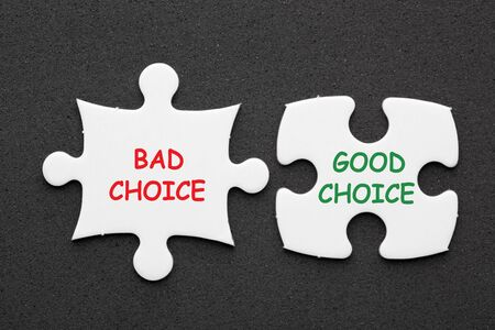 Bad Choice and Good Choice text in 2 pieces paper puzzle on black background. Business concept.