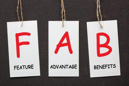 Acronym FAB - Feature Advantage Benefits written on paper labels set on black background. Business concept