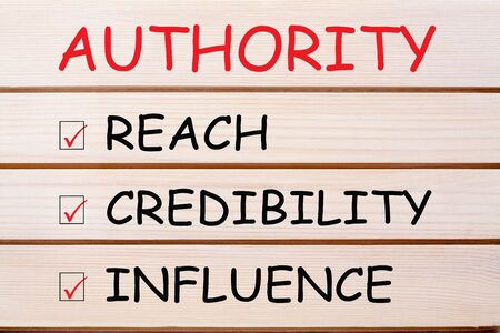 Authority with conceptual words reach, credibility and influence written on wood wall decor.