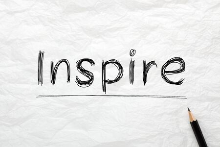 The word Inspire highlighted with pencil on wrinkled lined paper. Business concept. Zdjęcie Seryjne