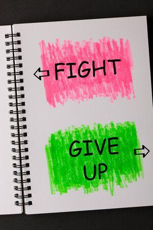 Fight or Give Up text on painted sketchbook in red and green. Business concept.