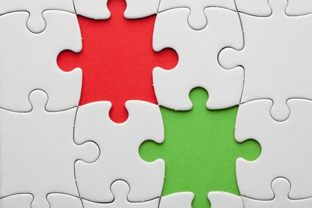 Jigsaw with missing pieces in red and green. Symbol of team work on a project in business.