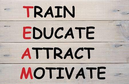 Acronym TEAM - Train, Educate, Attract, Motivate on wood planks grunge wall pattern. Stock fotó