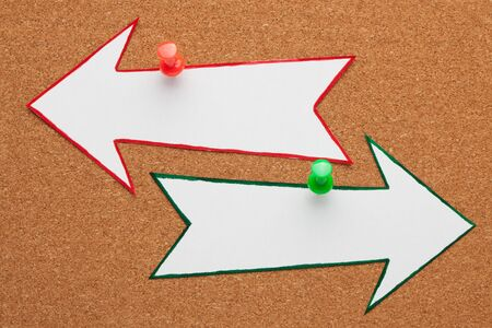 Blank opposite arrows pinned on cork board. Business concept Imagens