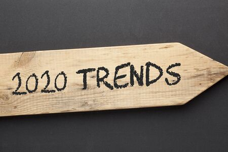 The text 2020 Trends written on old wooden arrow on black background.