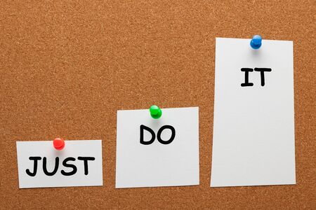 Just do it text on paper sheet with pin in the shape of a staircase on cork board. Business concept.