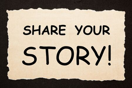 Share Your Story text on old torn paper on black background. Business concept. Imagens