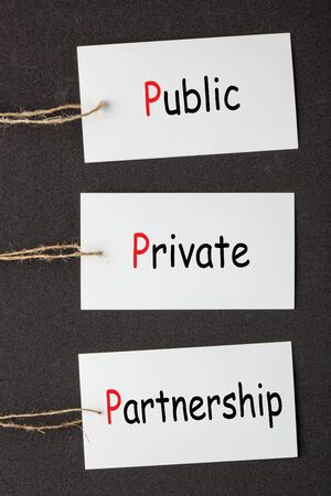 The words Public-Private Partnership (PPP) on set stickers with clip hanging on a rope on black background. Acronym business concept