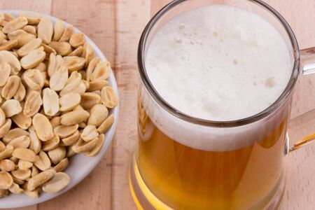 Glass of beer and roasted unsalted peanuts on wooden background. Selective focus Фото со стока