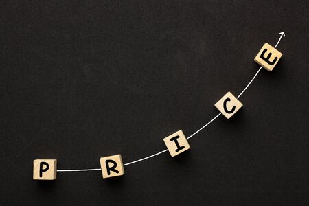 The word Price with directional arrow written on cubes shape wooden blocks on black background.