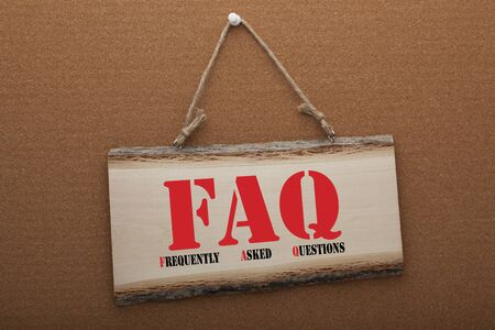 The acronym FAQ (Frequently Asked Questions) written in watercolor over a wooden sign hanging on a rope.