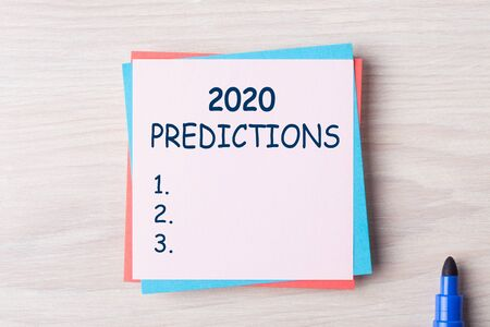2020 Predictions blank list on note on the wooden desk with felt-tip marker aside. Business concept Stockfoto - 130627417