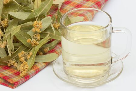 Linden tea in a glass cup, linden flower and leaf on white background. Фото со стока - 131981153