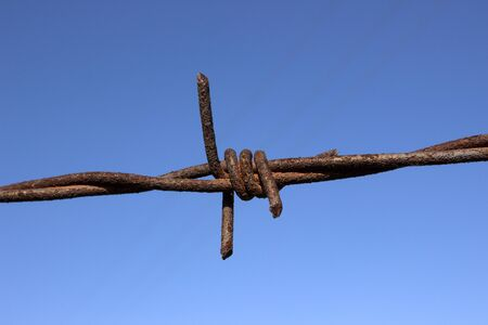 Rusty barbed wire and trace of the plane on the  background. Фото со стока - 131982264