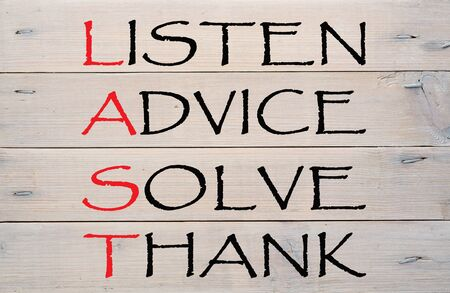 Listen, advice, solve and thank written on a wood planks grunge wall pattern. LAST acronym