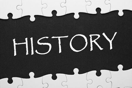 History sign and puzzle pieces over black surface. Фото со стока - 131982443