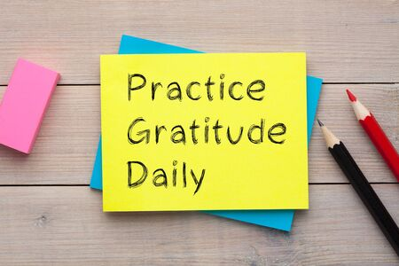 Practice Gratitude Daily written on the note with colorful pencils and eraser aside on wooden desk.  Stockfoto