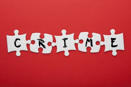 Crime word in pieces paper puzzle on red background. Business concept. Stockfoto