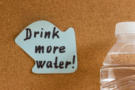 Drink more water handwriting on sticky note posted on cork board.
