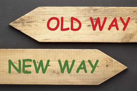 The words Old Way vs. New Way written on old wooden arrows on black background.