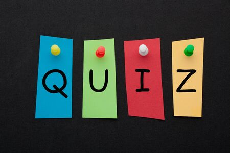Word quiz written in colorful stickers pinned on black background. Business concept Stockfoto - 131262524