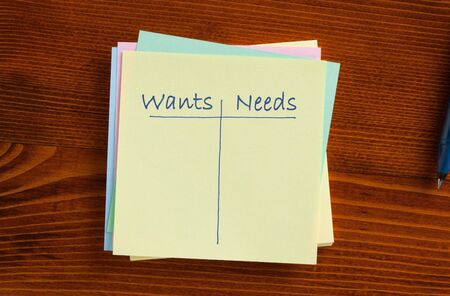 Wants vs. Needs written on note with pen aside. Business concept. Empty list