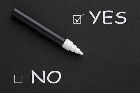 The words YES versus No written with white marker on black background. Фото со стока - 132487198