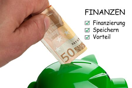 Hand putting banknote on a piggy bank and text Finance with keywords in German