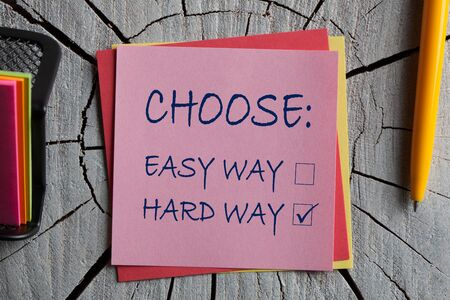 Choose easy way and hard way on note with pen and on wooden surface.