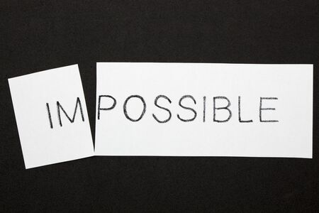 Changing word impossible transformed to possible on a white sheet. Business concept.