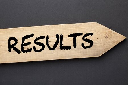 The word Results written on old wooden arrow on black background.