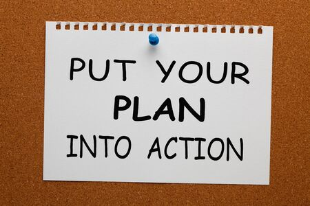 Put Your Plan Into Action text on white notebook paper pinned on cork board. Business concept
