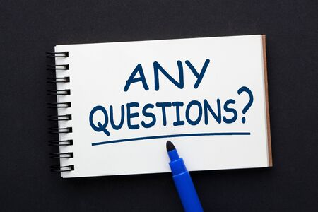 Text Any Questions written on notepad with blue felt-tip marker on black background. Business concept. Stockfoto