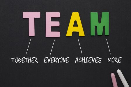 TEAM (Together, Everyone, Achieves, More) text spelled with alphabet letters on black background. Acronym business concept.