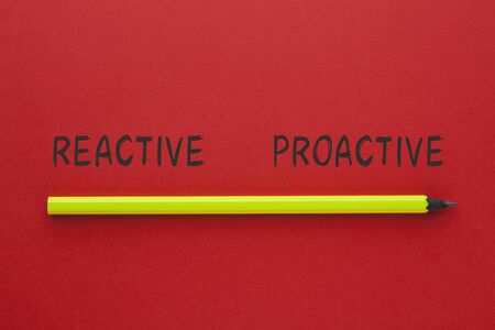 The words Reactive Proactive and pencil on red background. Business concept.