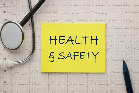 Health and Safety text on note with stethoscope and heartbeat rate, cardiogram and EKG concept.