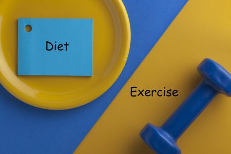 Exercise vs. Diet written on note in plate and dumbbell. Concept sport, diet, fitness, healthy eating.