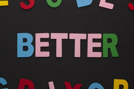 The word Better made of colorful alphabet letters on black background.