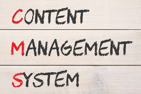 The words Content Management System on wood planks grunge wall pattern. Acronym CMS Фото со стока
