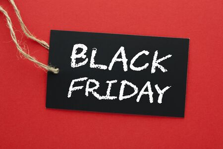 The words Black Friday on black tag hanging on a rope on red background.