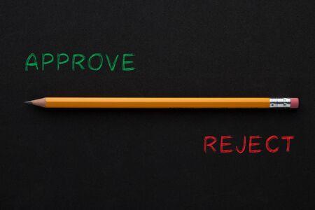 Les mots approuver ou rejeter avec un crayon sur fond noir. Concept d'entreprise.