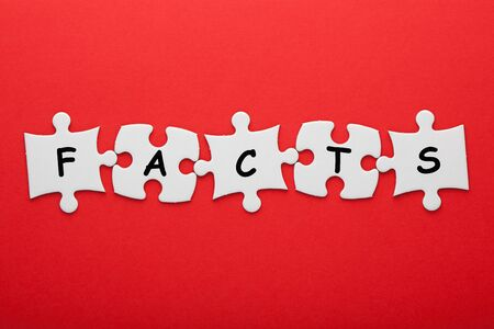 Facts word in pieces paper puzzle on red background. Business concept. Stock Photo