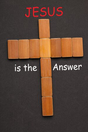 Jesus is the Answer text with cross made of blocks on black background.