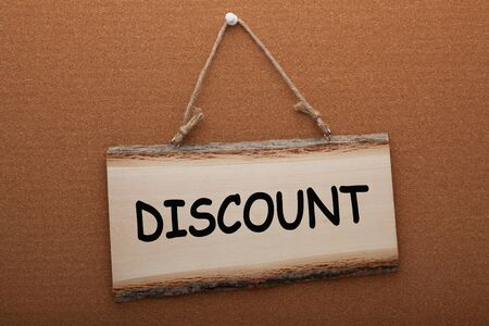 The word Discount written in watercolor over a wooden sign hanging on a rope.