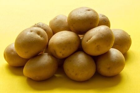 Bunch of  potatoes  on yellow background close up